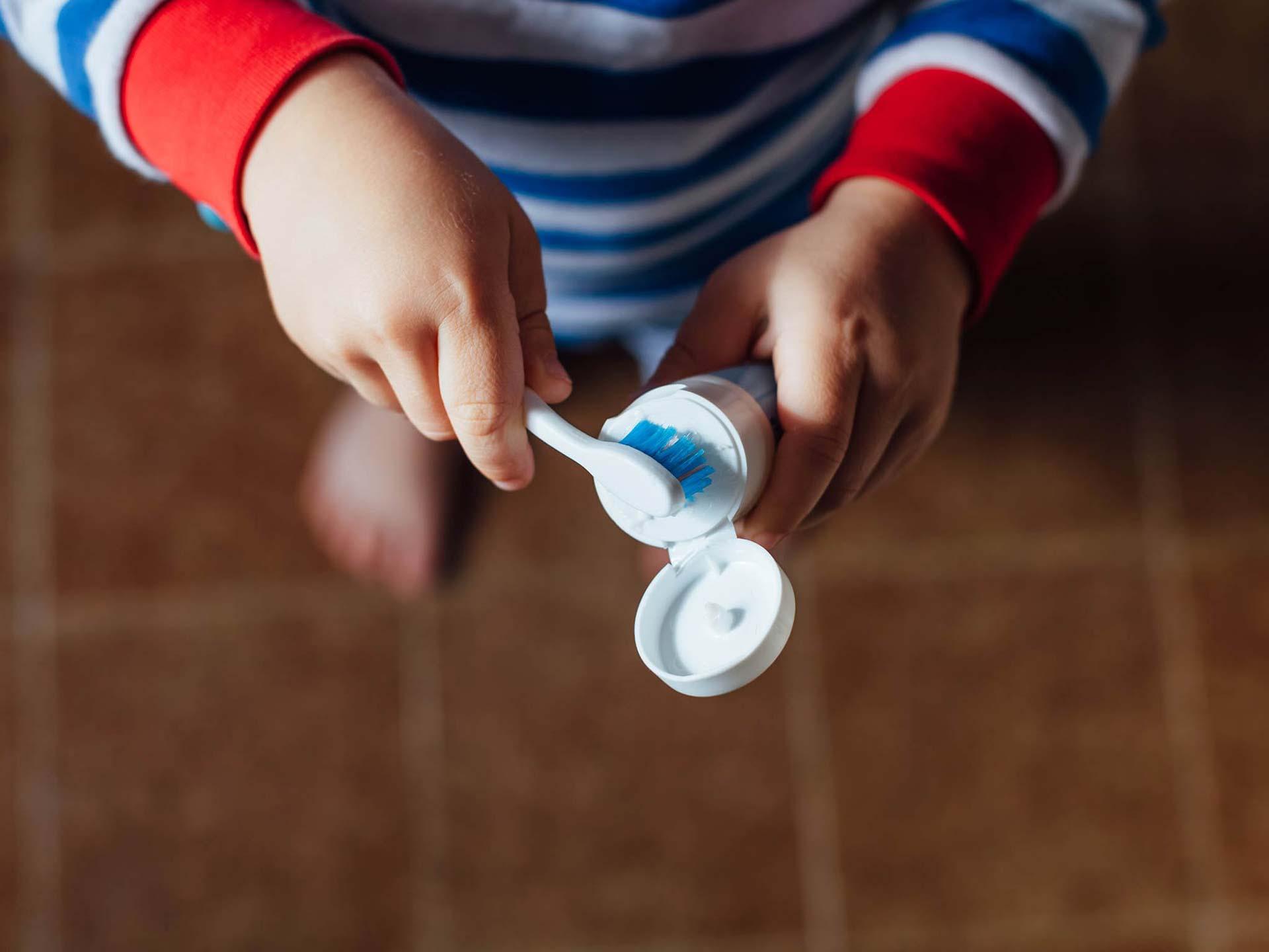 Mani di un bambino con spazzolino e dentifricio