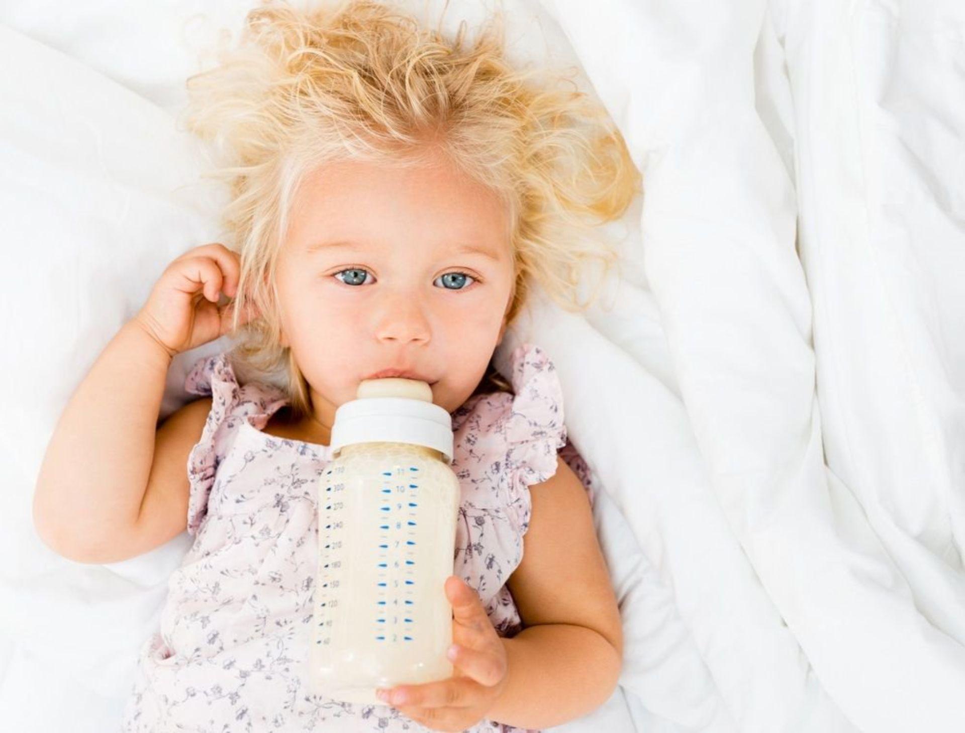 Bambina con biberon a letto